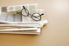 Tidning med glasögon på brun bakgrund Arkivbilder