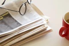Tidning med kaffe på brun bakgrund Arkivfoton