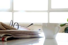 Tidning med kaffe på tabellen Fotografering för Bildbyråer