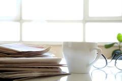 Tidning med kaffe på tabellen Arkivbild