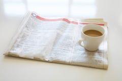 Tidning med kaffe på tabellen Arkivbilder