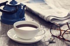 Tidning med kopp te Royaltyfria Bilder