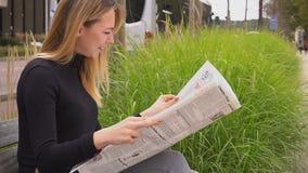 Tidning och sammanträde för kvinnlig person läs- på bänk nära vägen i ultrarapid lager videofilmer