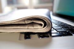 Tidning på ett bärbar datortangentbord Arkivbild