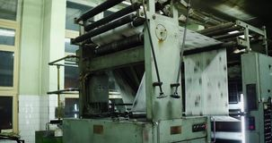 Tidningar fortskrider en monteringsband i en fabrik arkivfilmer