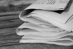 Tidningar på gammal wood bakgrund Svartvitt skott Fotografering för Bildbyråer