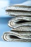 Tidningar vikta och som staplas på tabellen Arkivbild