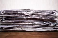 Tidningar vikta och som staplas på trätabellen Fotografering för Bildbyråer