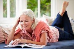 Tidskrift för åldrig kvinna för mitt som läs- ligger på soffan royaltyfri bild