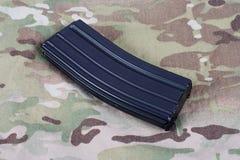 Tidskrift för gevär för USA-ARMÉ M-16 med kassetter på kamouflagelikformign Arkivbild