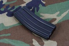 Tidskrift för gevär för USA-ARMÉ M-16 med kassetter på kamouflagelikformign Royaltyfri Bild