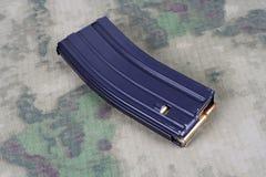 Tidskrift för gevär för USA-ARMÉ M-16 med kassetter på kamouflagelikformign Royaltyfria Foton