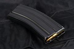 Tidskrift M-16 30. med ammo på den svarta likformign Royaltyfri Foto