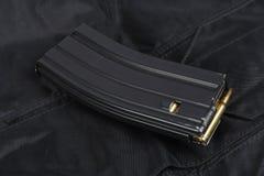 Tidskrift M-16 med ammo på den svarta likformign Royaltyfri Bild