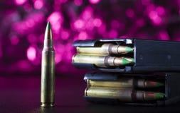 Tidskrifter AR-15 och ammo med en purpurfärgad bakgrund Arkivfoto