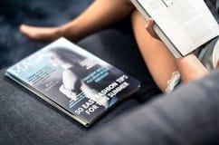 Tidskrifträkning med text och titlar på soffan Kvinnaläsningmode och skönhetartikel om senast trender royaltyfri bild