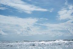 Tidvatten från stranden framme av blå himmel med moln Royaltyfri Foto