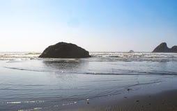Tidvatten som sveper på kusten med enormt, vaggar att sticka ut ut ur havet royaltyfria bilder