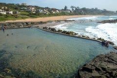 Tidvattens- pöl mot stranden och kust- länder för bostads- byggnader royaltyfri foto