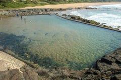 Tidvattens- pöl mot stranden och kust- länder för bostads- byggnader royaltyfria foton