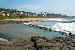 Tidvattens- pöl mot stranden och kust- länder för bostads- byggnader arkivfoton