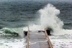 Tidvattens- vågor rusade pir under havsstorm Fotografering för Bildbyråer