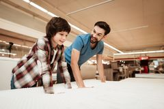 Tidy bearded father with young son is testing mattress for softness. Testing softness of mattress. Choosing mattress in store Stock Images