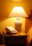 Tidy lamplit bedside table Royalty Free Stock Photography