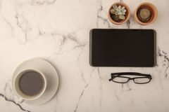 Tidy office desk with tablet and coffee. On marble background royalty free stock photo