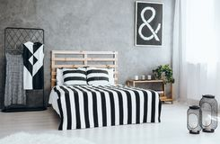 Tidy stylish bedroom. Big metal lanterns with candles standing on the floor in tidy stylish bedroom Stock Photography