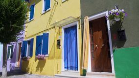 Tidy well-kept houses colored in bright vivid colors decorated with flowers