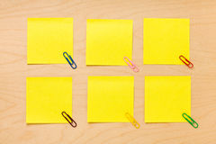 Tidy Yellow Post-it Collection. Set of six well-ordered square yellow blank post-it notes with colored clips arranged on a wooden board and ready to take a note Royalty Free Stock Photo