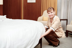 Tidying up the bed in room Stock Images