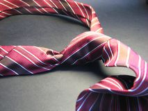 Tie 3. Red striped tie on the black shadow background royalty free stock images