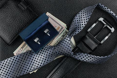 Tie, belt, wallet, cufflinks, money lying on the skin Stock Image