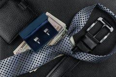 Tie, belt, wallet, cufflinks, money lying on the skin Stock Image