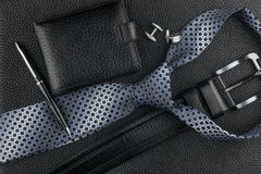 Tie, belt, wallet, cufflinks, pen lying on the skin Royalty Free Stock Images