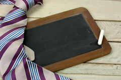 Tie and blackboard on wooden background Stock Photo