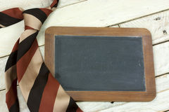Tie and blackboard on wooden background Royalty Free Stock Photography