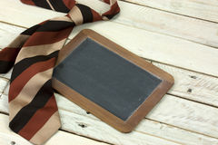 Tie and blackboard on wooden background Stock Images