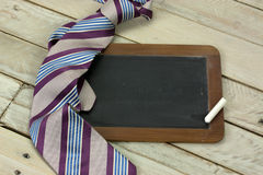 Tie and blackboard on wooden background Royalty Free Stock Image