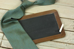 Tie and blackboard on wooden background Stock Image