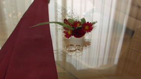 Tie the boutonniere and rings lie on the glass table of the groom stock footage