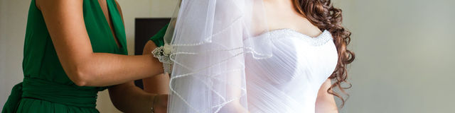 Tie a corset the bride. Royalty Free Stock Photo