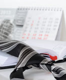 Tie on a diary. Cnhiped black and white tie on an opened diary Royalty Free Stock Image