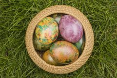 Tie-dyed Easter Eggs. In Wicker Basket in grass stock images