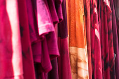 Tie dyed t-shirts and dresses hanging out for display Royalty Free Stock Image