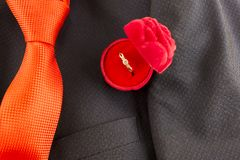 Tie, jacket and ring for the offer of the hand and heart Orange stock photography