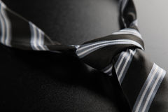 Tie knot with stripes. Elegant casual neck tie knot with stripes on black table royalty free stock photo