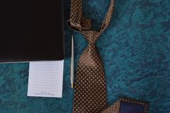 Cravat and notebook. Tie and laptop on blue background Stock Photos